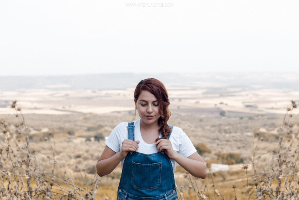 redhead in dungaree at yellow summer fields